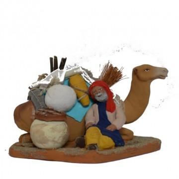 bédouin assis avec son dromadaire chargé couché