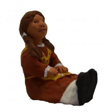 la petite fille aux couettes assise jambes tendues
