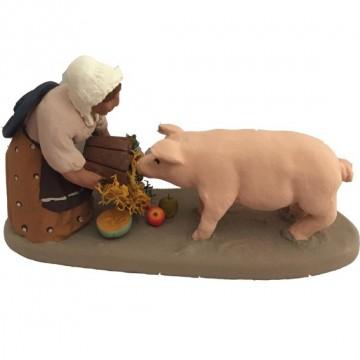 Fermière donnant à manger au cochon